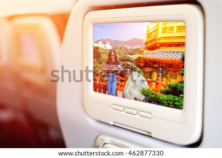 Aircraft monitor in front of passenger seat showing girl reading a map in looking for a way to Gold Chinese pavilion Temple at the park in Hong Kong