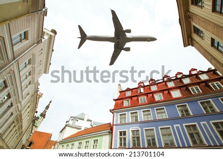 aircraft over Tallinn. over the streets of the old town is flying the plane - stock photo