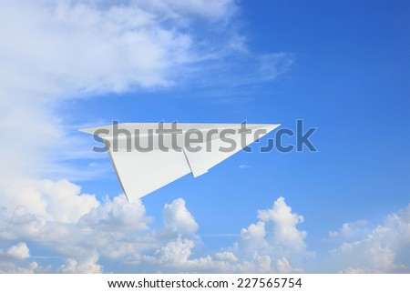 Aircraft paper plane flying in clear blue sky and bright cloudy space background, uses imagery concept to create a lyrical emotion winner crash success business. - stock photo