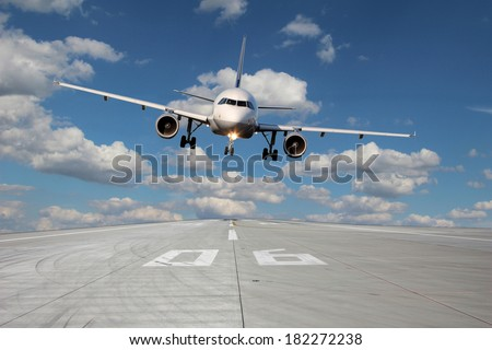 Aircraft passes low over runway 06 with beautiful clouds in the background - stock photo