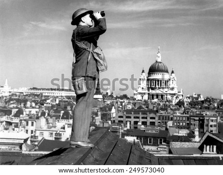 Aircraft spotter searches the sky with binoculars during the Battle of Britain. St. Paul's Cathedral is in the background. World War 2, ca. 1940-41. - stock photo