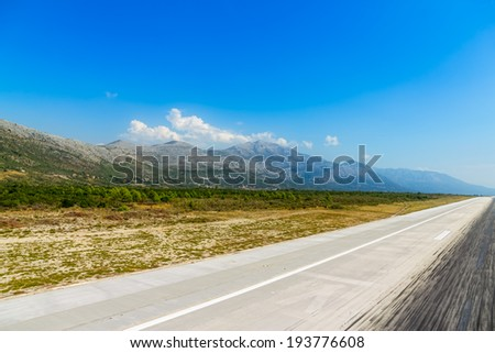 Aircraft tire tracks at airport runway landing zone with a view of a landscape - stock photo