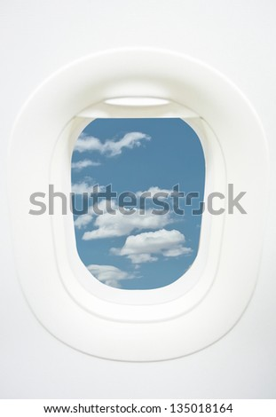 Aircraft Window with plane cruising against bright blue sky - stock photo