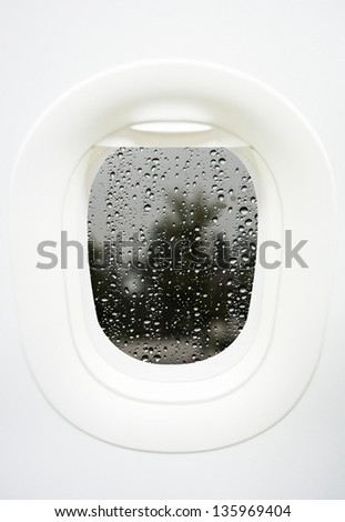 Aircraft Window with plane with rainy window and raindrops - stock photo