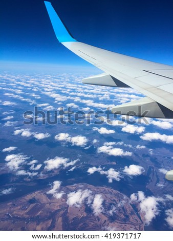 Aircraft wing and clouds, Wing aircraft in altitude during flight, Aircraft wing flying over clouds, Aircraft wing on cloudscape and blue sky, Aircraft wing on the clouds, flying background, window
