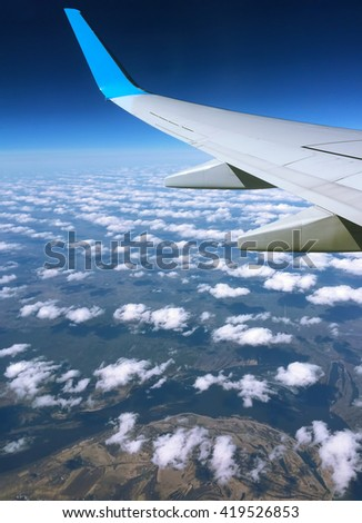 Aircraft wing and clouds, Wing aircraft in altitude during flight, Aircraft wing flying over clouds, Aircraft wing on cloudscape and blue sky, Aircraft wing on blue clouds, flying background, window