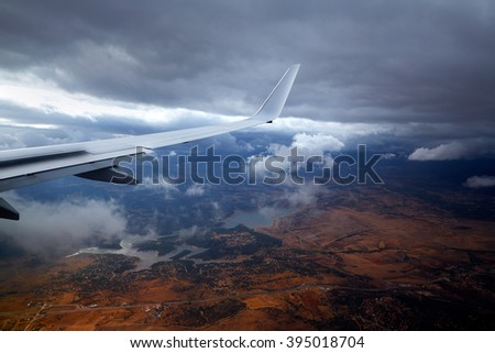 Aircraft wing in a cloudy stormy clouds sky flying - stock photo