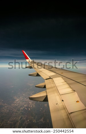 Aircraft wing on town, flying background