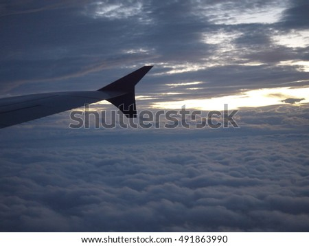 aircraft wing with sky clouds background