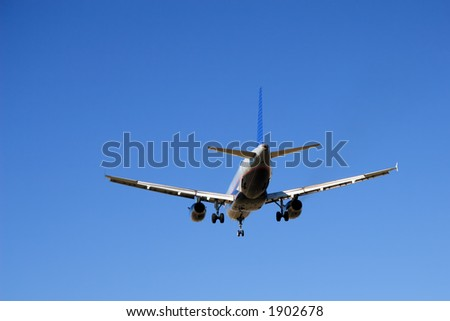 Aircraft with its landing gear down against a blue sky.