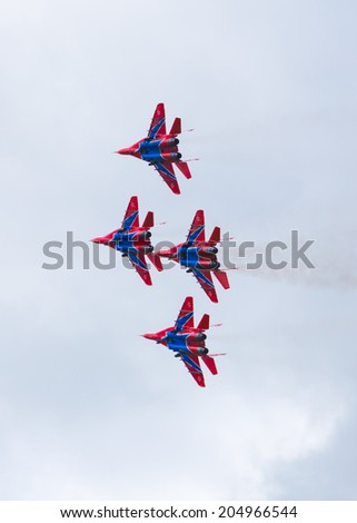 "Airfield Frolovo,Russia - June 29,2014.Festival ""Wings of Parma 2014"".stunt lozenge execution aerobatic team bright ""Swifts"""