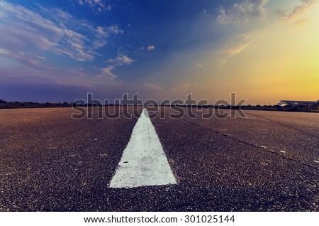 airfield runway leading toward fascination sunset - stock photo