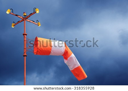Airfield sign of the direction and force of the wind against cloudy blue sky - stock photo