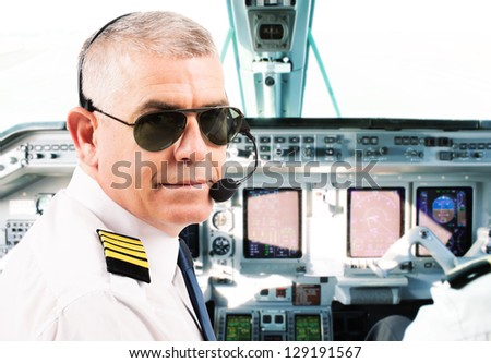Airline pilot wearing uniform with epaulettes and headset working in airliner during flight.