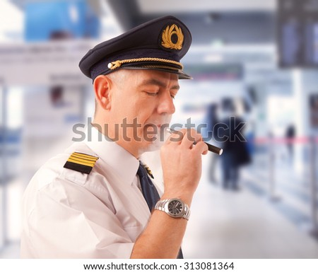 Airline pilot wearing uniform with epaulettes smoking electronic cigarette. - stock photo