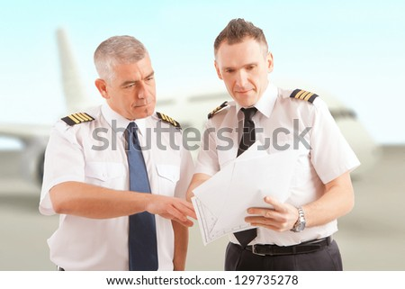 Airline pilots wearing uniform with epaulettes checking papers, passenger aircraft in background - stock photo