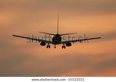 Airliner against sunset sky - stock photo