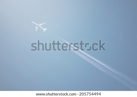 Airliner at high altitude with white condensation trails, on blue sky - stock photo