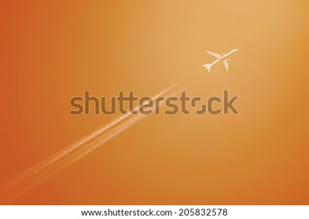 Airliner at high altitude with white condesation trails on orange filtered sky - stock photo