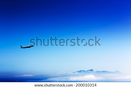 airliner in the stratosphere  over the mountains and clouds - stock photo