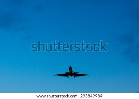 Airliner preparing for landing, view from below - stock photo