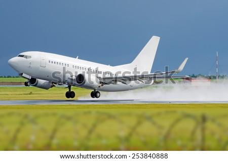 Airplane airport flight takeoff rain splashes - stock photo