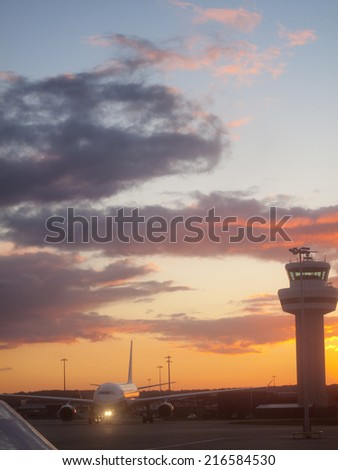 Airplane and air traffic control tower at airport - stock photo