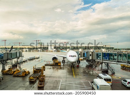 airplane and airport vehicles in beautiful light after rain - stock photo