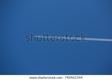 airplane and vapour trail in a clear blue sky