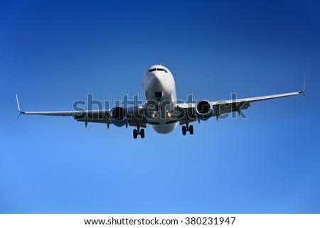 Airplane approaching airport - against clear blue sky