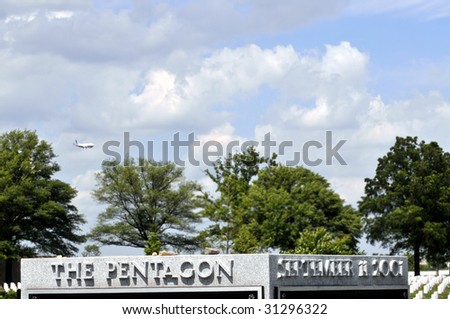 """Airplane approaching Washington DC, seen behind the September 11 memorial - """"the Pentagon Group Burial Marker"""" - at the Arlington National Cemetery in Arlington, Virginia, near Washington DC - stock photo"""