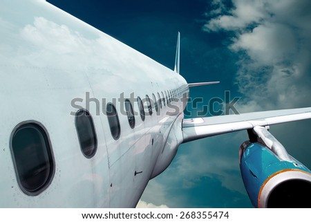 Airplane at flying under sky with clouds - stock photo