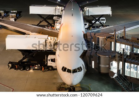 Airplane at gate during delivery catering service at night - stock photo