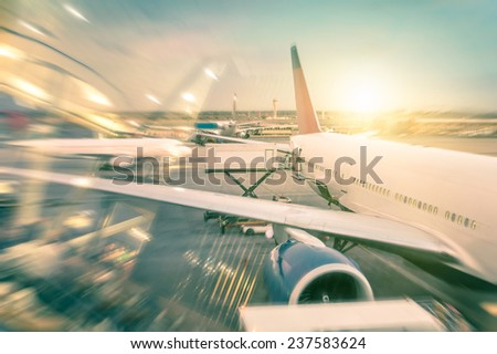 Airplane at the terminal gate preparing the takeoff - Modern international airport with boarding aircraft during sunset - Concept of alternative lifestyle and permanent traveling around the world - stock photo