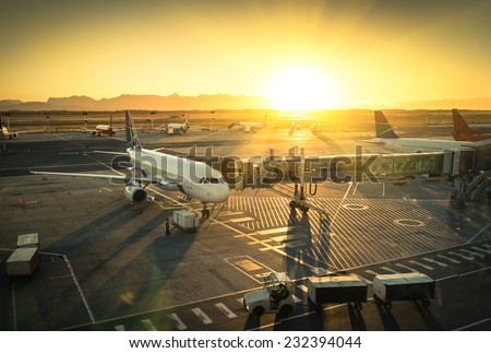 Airplane at the terminal gate ready for takeoff - Modern international airport during sunset - Concept of emotional travel around the world - stock photo