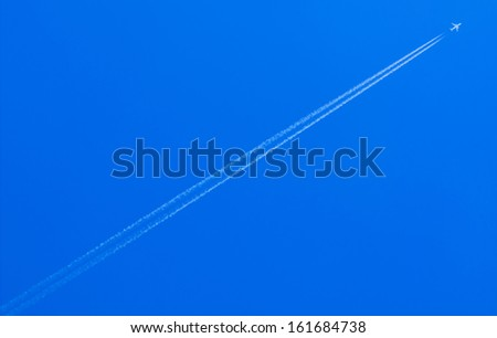 airplane condensation trail going up on blue sky - stock photo