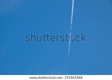 Airplane condensation trail or contrail with line of cloud over blue sky background - stock photo