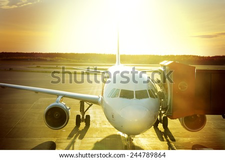 Airplane connected to gate bridge - stock photo