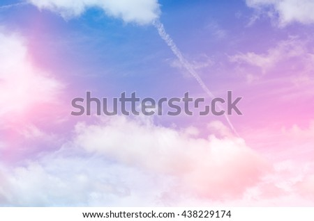 Airplane contrail against beautiful blue sky with delicate clouds - stock photo