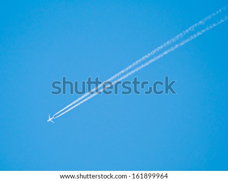 airplane contrail on blue Sky background - stock photo