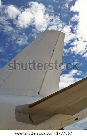 Airplane detail on cloudy blue sky