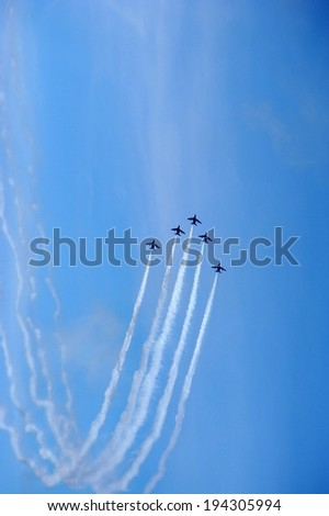 Airplane display team flying in formation with smoke trails. - stock photo