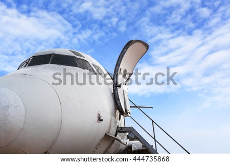 airplane door of private jet and open ladder at the airport on bule sky background, for travel concept