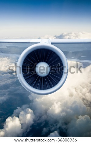 Airplane engine and wings on the blue sky and white clouds
