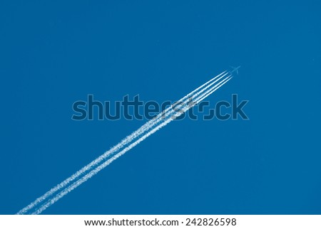 Airplane flies highly and leaves also inversion trace from engines - stock photo