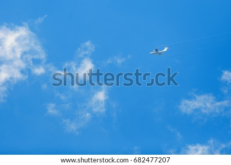 Airplane flies on a blue sky background.