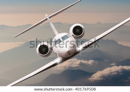 Airplane fly over clouds and Alps mountain on sunset. Front view of a big passenger or cargo aircraft, business jet, airline. Transportation and travel concept. - stock photo