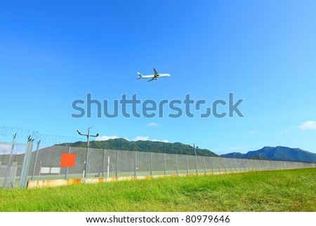Airplane fly over grasses at day time - stock photo