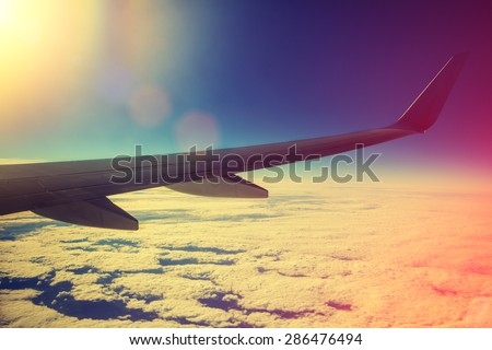 Airplane flying above clouds at pink sunrise - stock photo