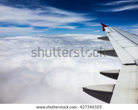 Airplane flying above cloudy, space left of frame.